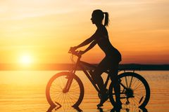 Silhouette of a sporty girl in a suit that sits on a bicycle in the water at sunset on a warm summer day. Fitness concept. Sky bac. The silhouette of a sporty Stock Images