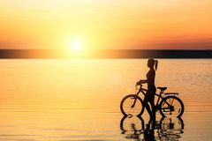 Silhouette of a sporty girl in a suit that sits on a bicycle in the water at sunset on a warm summer day. Fitness concept. Sky bac Stock Photography