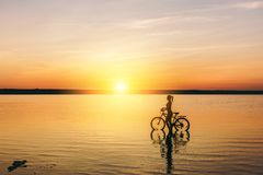 Silhouette of a sporty girl in a suit that sits on a bicycle in the water at sunset on a warm summer day. Fitness concept. Sky bac Stock Photo