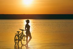 Silhouette of a sporty girl in a suit standing near a bicycle in the water at sunset on a warm summer day. Fitness concept. Sky ba Stock Photos
