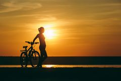 Silhouette of a sporty girl in a suit standing near a bicycle in the water at sunset on a warm summer day. Fitness concept. Sky ba. The silhouette of a sporty Stock Photos