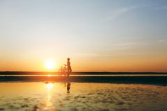 Silhouette of a sporty girl in a suit standing near a bicycle in the water at sunset on a warm summer day. Fitness concept. Sky ba. The silhouette of a sporty Royalty Free Stock Photography