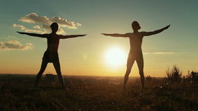 Silhouette of sporty man and woman doing triangle pose in the park at sunset stock video