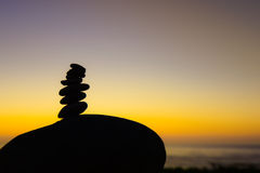 Silhouette stack of small rocks on a large rock at sunset Royalty Free Stock Image