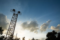 Silhouette of stadium halogen spotlight tower. Silhouette of outdoor stadium halogen spotlight tower and sky clouds in twilight Royalty Free Stock Image