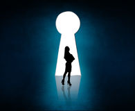 Silhouette stands near big keyhole exit. Royalty Free Stock Photos