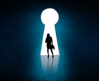 Silhouette stands near big keyhole exit. Royalty Free Stock Image