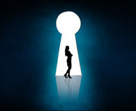 Silhouette stands near big keyhole exit. Stock Photos