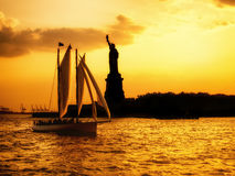 Silhouette of the Statue of Liberty and a sailboat at sunset Royalty Free Stock Photo