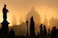 Silhouette of statue and tourists on Charles bridge during sunri Royalty Free Stock Photo