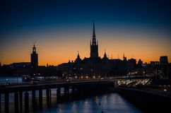 Silhouette of Stockholm cityscape skyline with Riddarholmen Church spires, City Hall Stadshuset tower, bridge over Lake Malaren in stock images