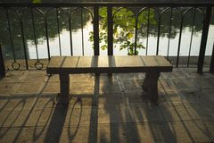 Silhouette stone park bench by lake at sunset.  Stock Photo