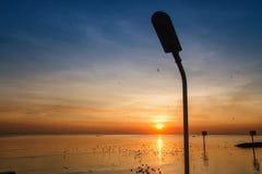Silhouette of streetlight with beautiful sunset twilight sky at Stock Photos
