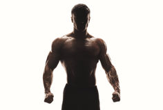 Silhouette of a strong man. Dark silhouette of a strong man on white background. Confident young fitness man with strong hands and clenched fists. Clipping path Stock Photography