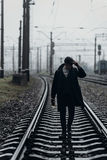 Silhouette of stylish man in retro look walking in rain on background of foggy railway. england in 1920s theme. fashionable. Brutal gangster. atmospheric stock photos