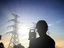 Silhouette Successful male engineer standing survey work on cons. Truction over blurred high-voltage pylons and construction. examination, inspection, survey Royalty Free Stock Image