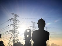 Silhouette Successful male engineer standing survey work on cons. Truction over blurred high-voltage pylons and construction. examination, inspection, survey Stock Photo