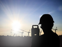 Silhouette Successful male engineer standing survey work on cons. Truction over blurred high-voltage pylons and construction. examination, inspection, survey Stock Photography