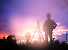 Silhouette Successful male engineer standing survey work on cons. Truction over blurred high-voltage pylons and construction. examination, inspection, survey Royalty Free Stock Photos