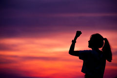 Silhouette of Successful woman with arm up.  stock photos