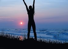 Silhouette of a Successful woman with Ocean as background. Silhouette of a woman with Ocean as background with her arms up representing success and happiness royalty free stock images