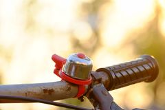 Close up a bicycle bell with an old rusty handlebar and silhouette sunset background royalty free stock photography