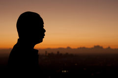 Silhouette Sunrise Man. Silhouette profile of a man at sunrise with urban city behind. Male Asian, Japanese stock photo
