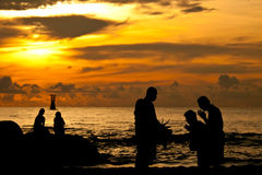 Silhouette sunrise of Monk and Buddist on the sea Royalty Free Stock Photos