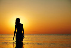 Silhouette at sunset. Silhouette of a girl in the water at sunset. Natural light and dark. Artistic colors added. Horizontal photo Royalty Free Stock Photography