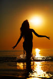 Silhouette at sunset. Silhouette of a girl in the water at sunset. Natural light and dark. Artistic colors added. Horizontal photo Stock Photos