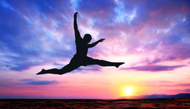 Silhouette at sunset. A silhouette of a jumping man on a colorful sunset background Stock Photo
