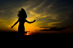 Silhouette at sunset. Girl with long hair dancing in the sunset Royalty Free Stock Image