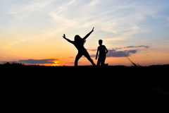 Silhouette at sunset. Girl with long hair dancing in the sunset Stock Image