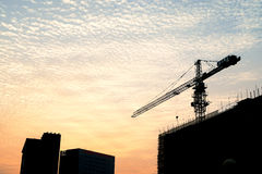 Silhouette of sunset scene with tower crane on the construction Stock Image