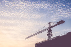 Silhouette of sunset scene with tower crane on the construction Stock Photo