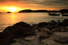 Silhouette sunset seascape at Lipe, Satun. Silhouette sunset seascape of natural stone arch on beach and wooden boats on Andaman sea at Koh Lipe, Satun, Thailand stock image