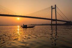 Silhouette sunset of Vidyasagar bridge with a boat on river Hooghly. Silhouette Vidyasagar setu bridge with a wooden country boat on river Hooghly at sunset royalty free stock photography