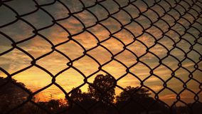 Silhouette. A sunset view through fence Royalty Free Stock Image