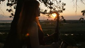 Silhouette at sunset young beautiful red-haired girl playing saxophoneon nature, a woman blowing into the pipe, concept hobby, mus stock video footage