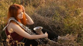 Silhouette at sunset young beautiful red-haired girl playing saxophoneon nature, a woman blowing into the pipe, concept hobby, mus stock footage