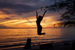 Silhouette at sunset of young woman jumping from a log of wood on the beach stock image