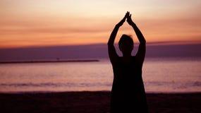 Silhouette supérieure asiatique faisant le namaste de méditation au beac de lever de soleil Images libres de droits