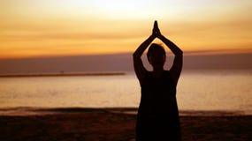 Silhouette supérieure asiatique faisant le namaste de méditation au beac de lever de soleil Image libre de droits