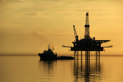 Silhouette of supply vessel and drilling platform Stock Photo