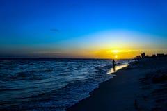 Silhouette sur une plage I de coucher du soleil Photos libres de droits