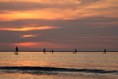 Silhouette of surf boys in the evening sun Stock Photo