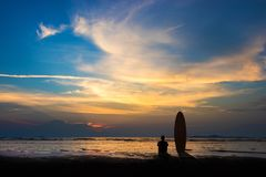 Silhouette of surf man sit with a surfboard on the beach. Surfing scene at sunset beach with colorful sky. Outdoor water sport adventure lifestyle.Summer Royalty Free Stock Images