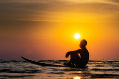 Silhouette of surf man sit on a surfboard. Surfing at sunset. Beach. Outdoor water sport adventure lifestyle.Summer activity. Handsome Asia male model in his Stock Photography