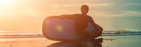 Silhouette of surf man sitting with a surfboard on the seashore beach at sunset time BANNER, long format royalty free stock photos