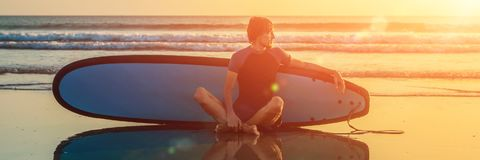 Silhouette of surf man sitting with a surfboard on the seashore beach at sunset time BANNER, long format stock image